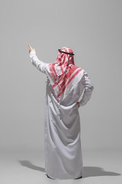 Une Personne Arabe Posant Vue Arrière Isolée Sur Studio Gris Photo gratuit