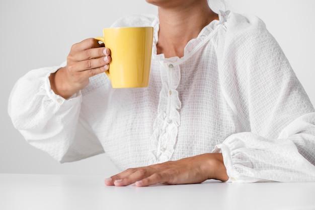 Personne en chemise blanche tenant une tasse Photo gratuit