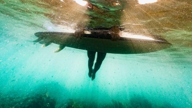 Personne Couchée Sur Une Planche De Surf Dans L'eau De Mer Bleue Photo gratuit