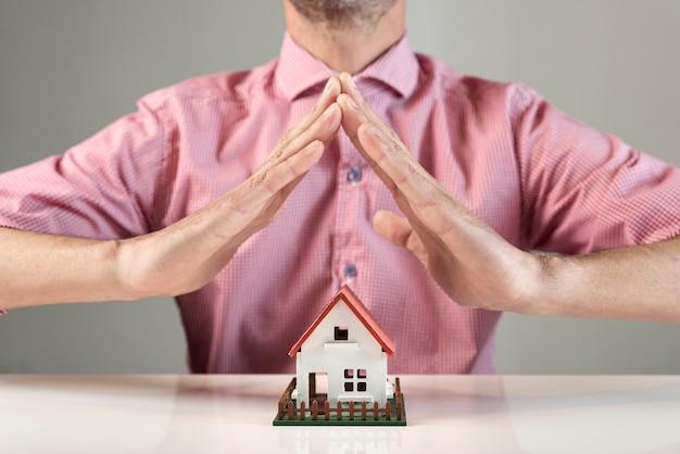 Personne créant un toit pour la maison avec ses mains Photo gratuit