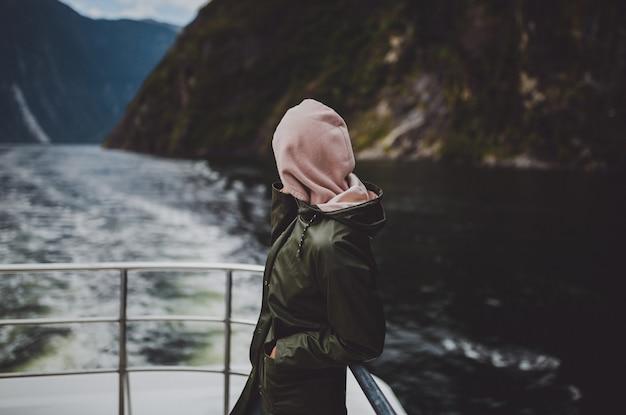 Personne Dans Un Sweat à Capuche Debout Sur Le Navire Pendant La Croisière à Milford Sound En Nouvelle-zélande Photo gratuit