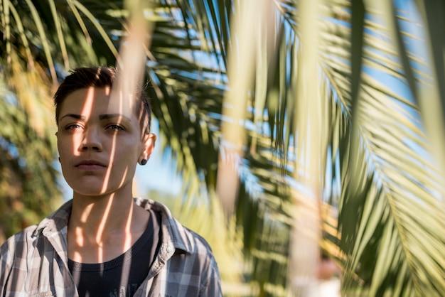Personne debout dans l'ombre des branches de palmier Photo gratuit