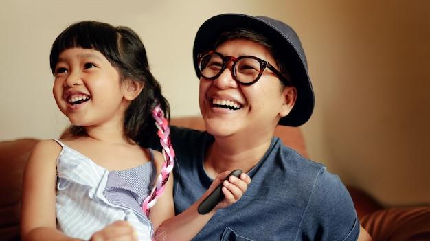Personne heureuse, une jolie fille souriante assise sur un canapé avec son parent. Photo Premium