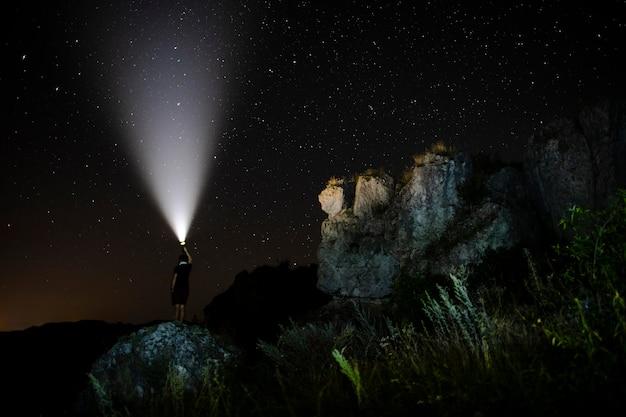 Personne avec une lampe de poche dans la nature Photo gratuit