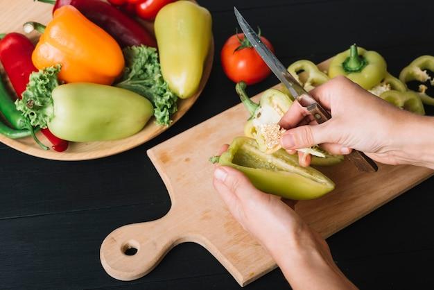 Une personne 'main avec un couteau tenant le poivron sur le comptoir de cuisine noir Photo gratuit