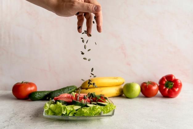 Personne, main, saupoudrer, graines, citrouille, sur, salade légume Photo gratuit
