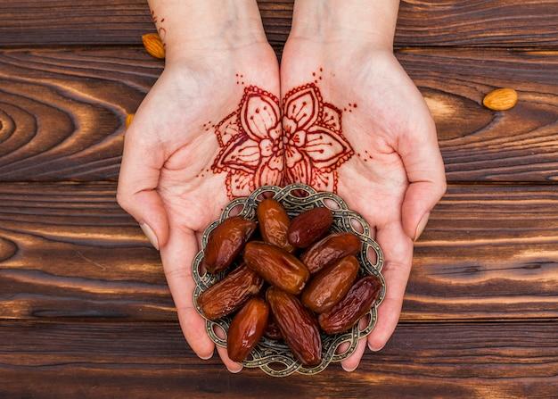 Personne avec mehndi tenant une assiette avec des fruits de dates Photo gratuit