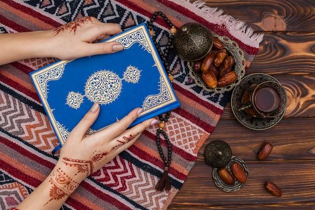 Personne avec mehndi tenant le coran près d'une tasse de thé Photo gratuit