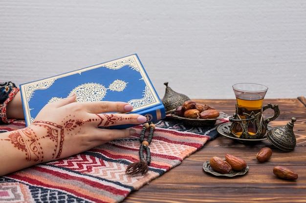 Personne avec mehndi tenant le coran près d'un verre à thé Photo gratuit