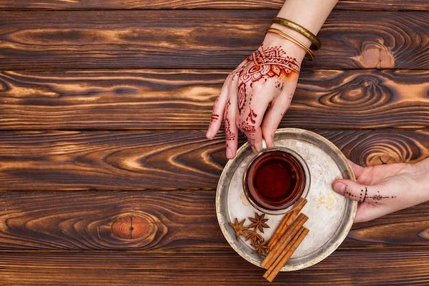 Personne avec mehndi tenant une tasse de thé sur une grande assiette Photo gratuit