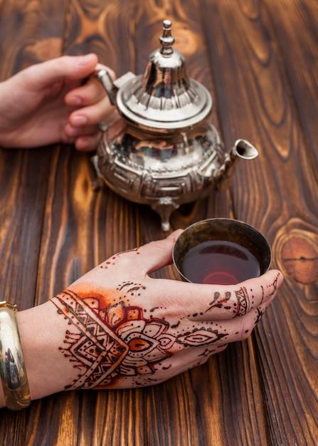 Personne avec mehndi tenant une théière et une tasse Photo gratuit