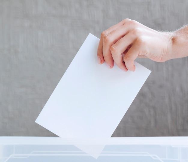 Personne mettant un bulletin de vote vide dans une boîte Photo gratuit