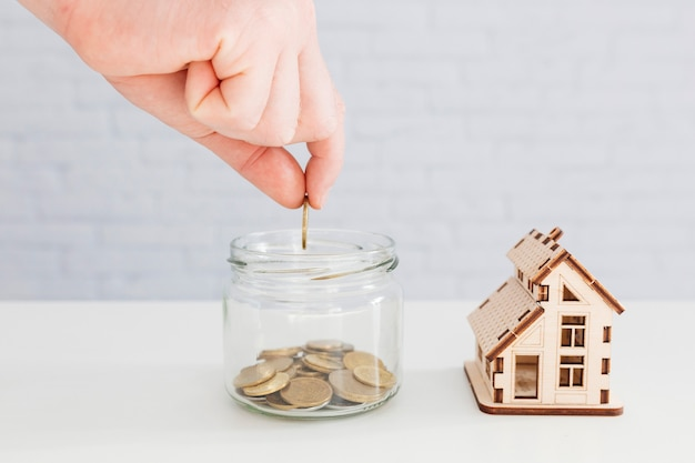 Personne mettant des pièces de monnaie dans le pot Photo gratuit