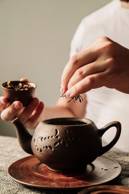 Personne, mettre, thé, herbes, gros plan, théière Photo gratuit