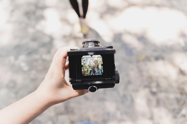 Une personne montrant la photo d'une femme sur appareil photo vintage Photo gratuit