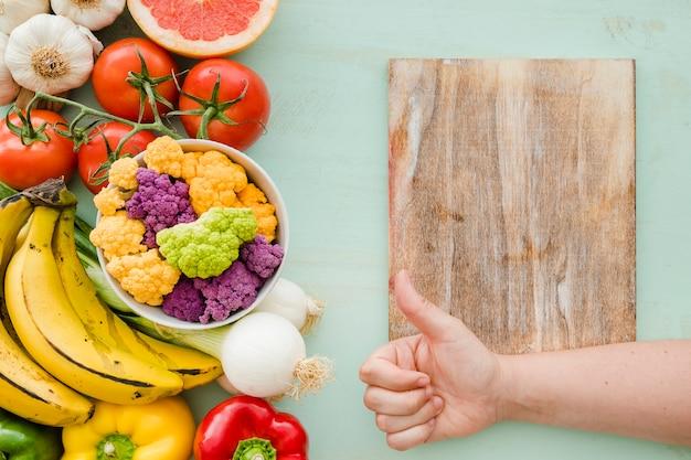 Une personne montrant signe de pouce sur la table à découper et des aliments sains et frais Photo gratuit