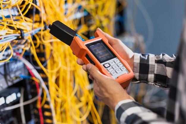 Personne montrant un testeur de fibre optique Photo gratuit