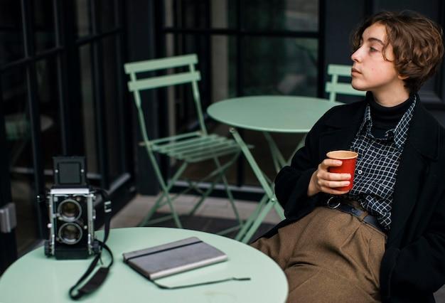 Personne Non Binaire Portant Des Vêtements Rétro Et Dégustant Un Café Photo gratuit