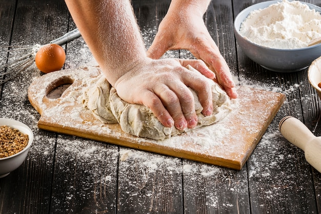 Une personne préparant la pâte à pain sur une planche à découper Photo gratuit