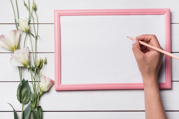 Une personne qui écrit sur un tableau blanc avec un crayon sur un fond en bois Photo gratuit
