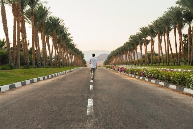 Personne Qui Marche Sur La Route Avec Des Palmiers Sur Les Côtés Avec Un Beau Paysage De Coucher De Soleil Photo gratuit