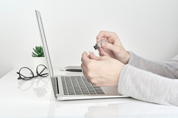 Personne qui ouvre un flash usb à côté d'un ordinateur portable, concept office work Photo Premium