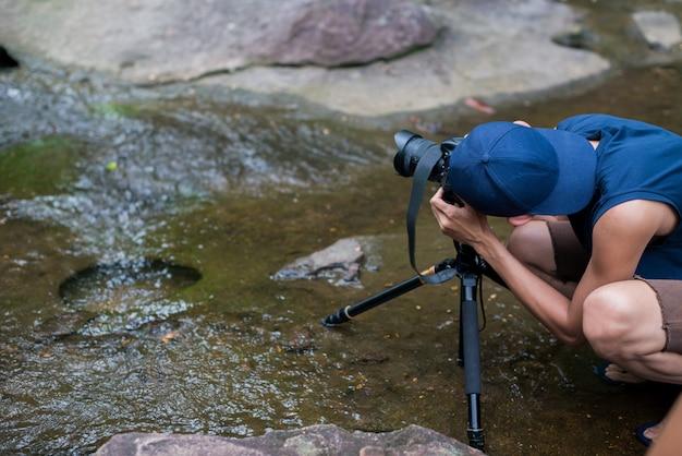 Personne qui utilise l'appareil photo pour prendre des photos d'une cascade en forêt Photo Premium