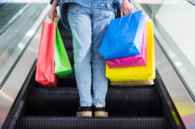 Personne avec des sacs sur l'escalier roulant Photo gratuit