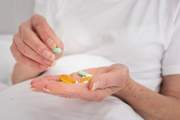 Personne tenant beaucoup de pilules colorées Photo gratuit