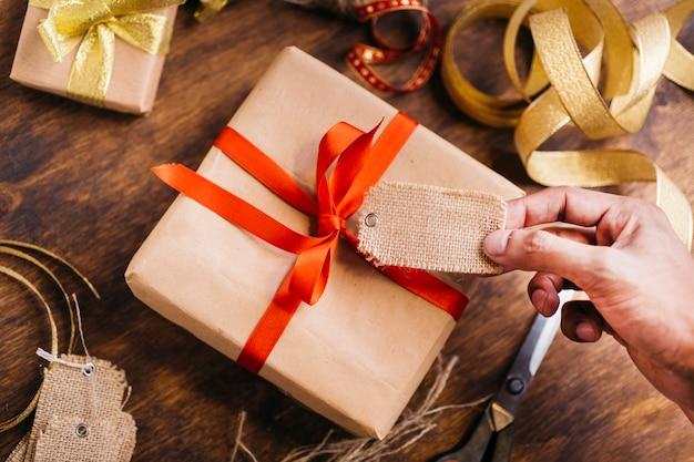 Personne tenant l'étiquette au-dessus d'une boîte cadeau Photo gratuit