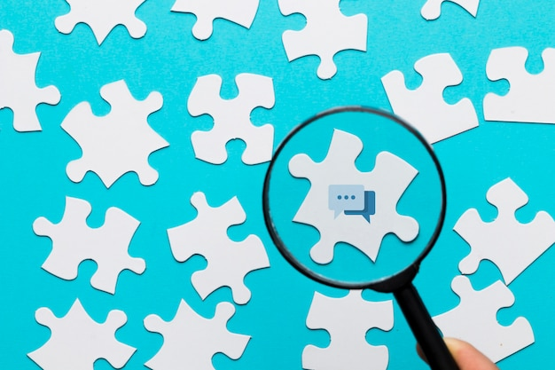 Une personne tenant une loupe sur l'icône du message sur un puzzle blanc sur fond bleu Photo gratuit