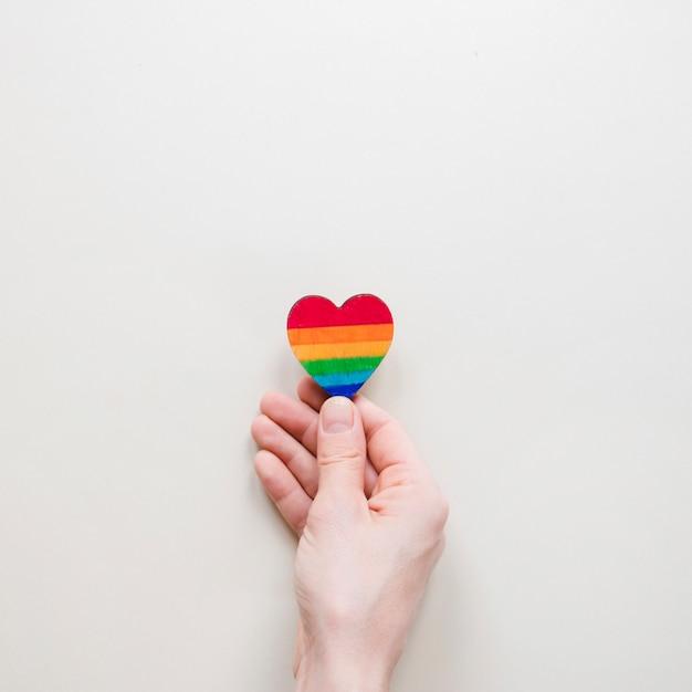 Personne tenant petit coeur arc-en-ciel Photo gratuit