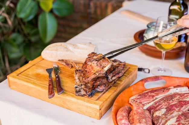 Une Personne Tenant Steak De Bœuf Grillé Frais Avec Tong Sur Planche De Bois Photo gratuit