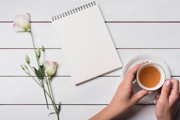 Une personne tenant une tasse de thé avec le bloc-notes en spirale et de belles fleurs sur le bureau en bois Photo gratuit