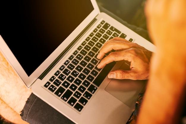 Personne travaillant à distance sur un ordinateur portable compact Photo gratuit