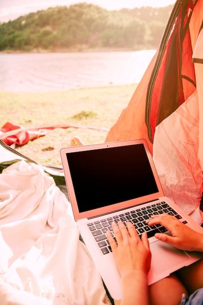 Personne travaillant sur un ordinateur portable à l'extérieur Photo gratuit