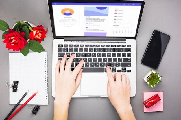 Personne travaillant sur un ordinateur portable à la table Photo gratuit
