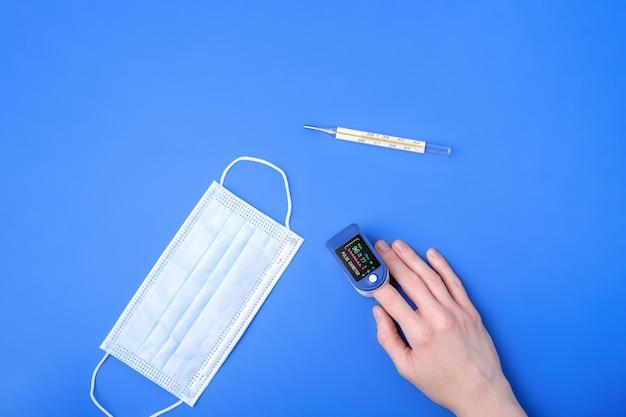 Personne Utilisant Le Dispositif D'oxymètre De Pouls Sur Le Doigt Près De Thermomètre Et Masque Médical, Concept De Surveillance Des Soins De Santé Photo Premium