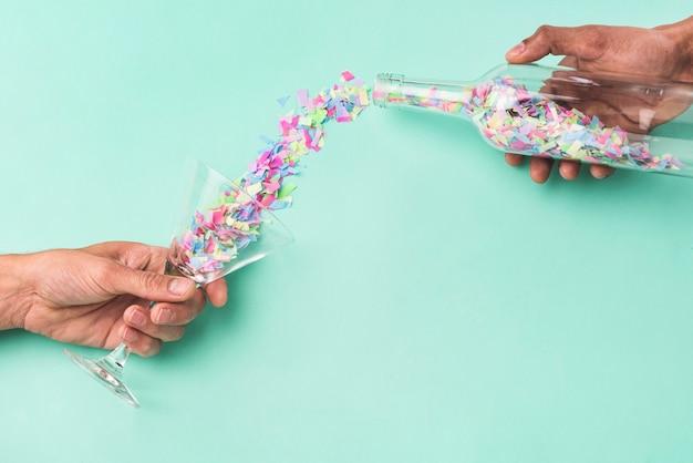 Personne Versant Des Confettis De La Bouteille Dans Le Verre Photo gratuit