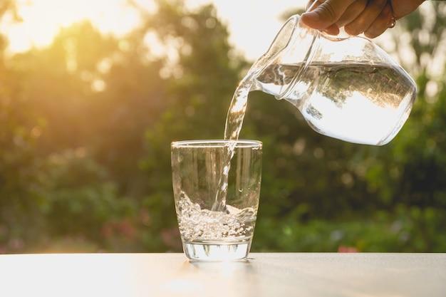 Personne versant de l'eau de pichet à verre sur fond de nature Photo Premium