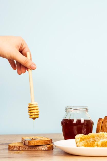 Une personne verse du miel sur une tranche de pain sur une table en bois Photo gratuit