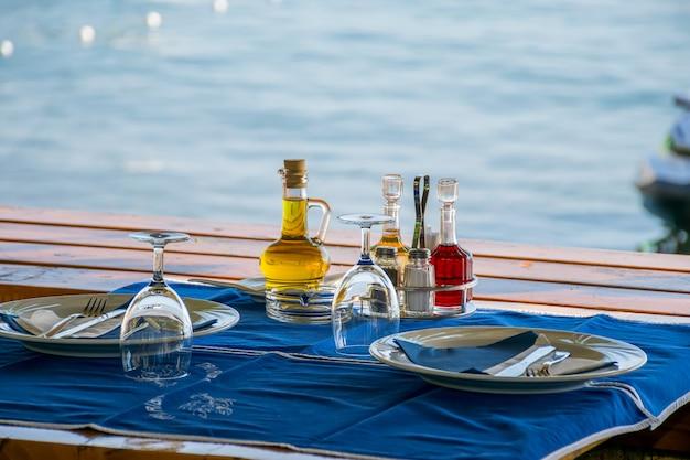 Le personnel du restaurant prépare ses tables près de la mer pour le dîner au coucher du soleil Photo Premium