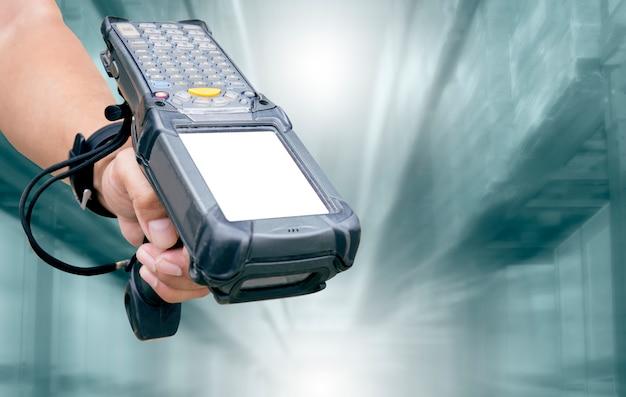 Le personnel de l'entrepôt tient un lecteur de code à barres sur le flou de l'entrepôt. Photo Premium
