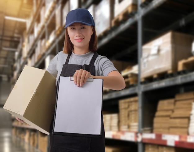 Personnel féminin livreur de produits signer la signature sur le formulaire de réception du produit avec les boîtes de colis. Photo Premium