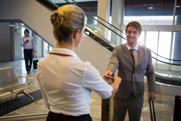 Personnel Féminin Vérifiant La Carte D'embarquement Des Passagers Au Comptoir D'enregistrement Photo gratuit
