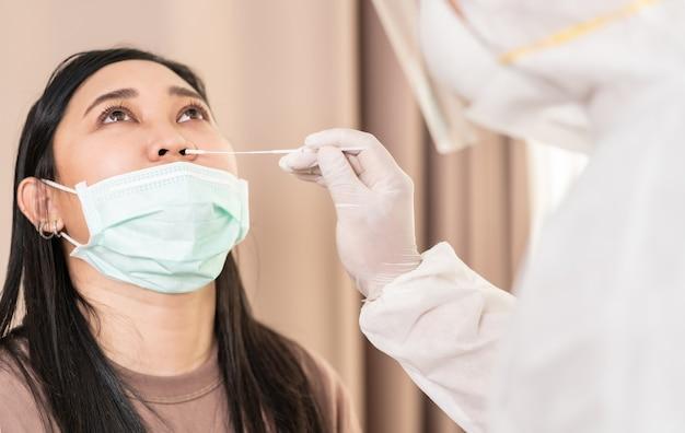 Le Personnel Médical Avec Une Combinaison Epi Teste Le Coronavirus Covid-19 à Une Femme Asiatique Photo Premium