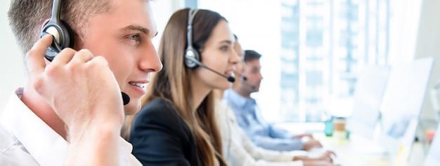 Personnel opérateur masculin avec centre d'appels travaillant en équipe Photo Premium