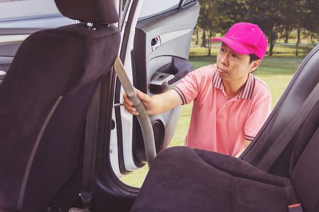 Personnel de service automobile nettoyage de l'intérieur de la voiture avec aspirateur Photo Premium