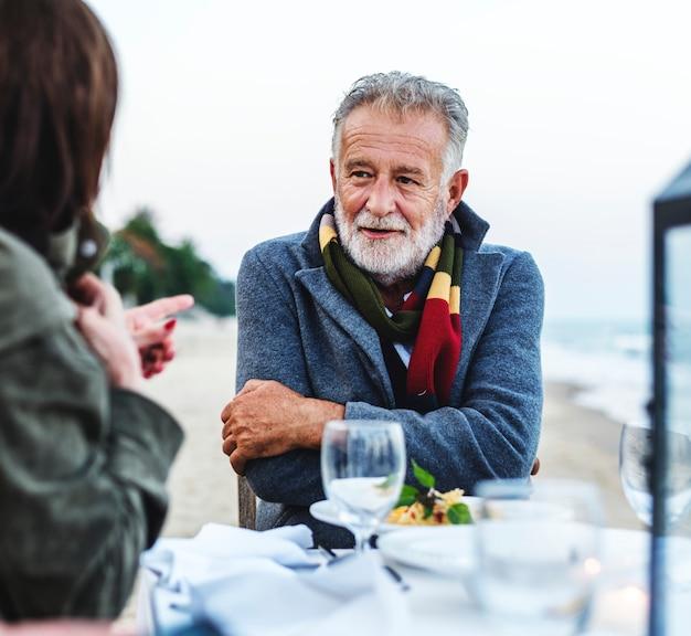 Personnes âgées ayant un dîner à la plage Photo Premium