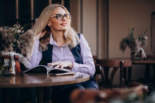 Personnes âgées Femme D'affaires Assis à L'extérieur Du Café Et Lire Le Magazine Photo gratuit